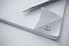 Bloco de notas com um ícone do smiley Fotografia de Stock