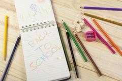 Bloco de notas com um colorido de volta à mensagem da escola nela Fotografia de Stock Royalty Free