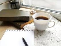 Bloco de notas, copo de café e livros vazios na soleira fotografia de stock royalty free