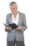 Bloco de notas de sorriso da leitura da mulher de negócios Imagem de Stock