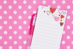 Bloco de notas do cora??o com a pena na tela brilhante do rosa e a branca do ?s bolinhas foto de stock royalty free