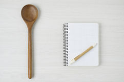 Bloco de notas e colher de madeira na tabela de madeira branca Foto de Stock