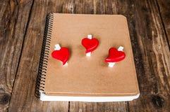 Bloco de notas e corações no fundo de madeira do grunge Fotos de Stock Royalty Free