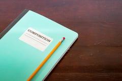 Bloco de notas e lápis da composição em uma tabela Imagens de Stock