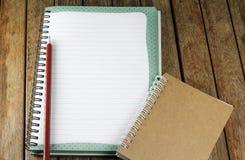 Bloco de notas e lápis em uma mesa Imagem de Stock