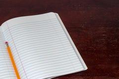 Bloco de notas e lápis em uma tabela Imagem de Stock