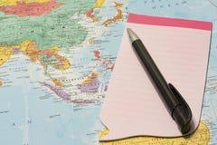 Bloco de notas e pena cor-de-rosa sobre o mapa Fotos de Stock Royalty Free