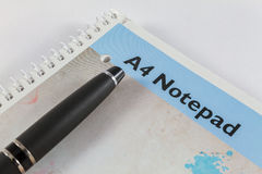 Bloco de notas A4 e pena preta no fundo branco Fotos de Stock Royalty Free