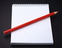 Bloco de notas em branco e um lápis no preto Fotografia de Stock Royalty Free