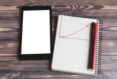 bloco de notas em que o gráfico com a seta vermelha do crescimento de lucro é tirado e a mentira do portátil na tabela foto de stock