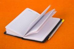 Bloco de notas em um fundo alaranjado Caderno e lápis Escola e instrução stationery fotografia de stock