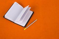 Bloco de notas em um fundo alaranjado Caderno e l?pis Escola e instru??o stationery imagens de stock