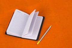Bloco de notas em um fundo alaranjado Caderno e l?pis Escola e instru??o stationery fotos de stock royalty free