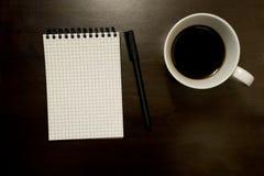 Bloco de notas espiral gridded vazio com pena e xícara de café - na madeira escura imagens de stock royalty free