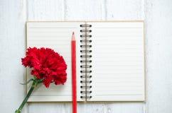 Bloco de notas, lápis e flores do cravo Foto de Stock