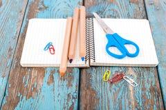 Bloco de notas, lápis, tesouras, clipes de papel Suppli do escritório ou da escola Fotos de Stock Royalty Free