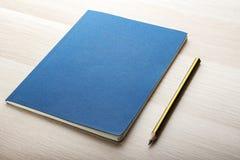 Bloco de notas na mesa de madeira com lápis fotografia de stock royalty free