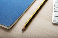 Bloco de notas na mesa de madeira com lápis fotos de stock