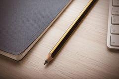 Bloco de notas na mesa de madeira com lápis imagens de stock
