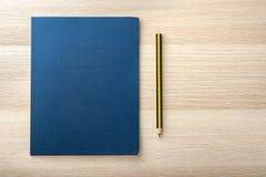 Bloco de notas na mesa de madeira com lápis imagem de stock