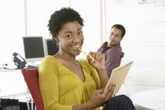 Bloco de notas novo de sorriso de Holding Pencil And da mulher de negócios Imagens de Stock Royalty Free