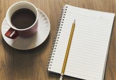 Bloco de notas, pena e xícara de café na tabela de madeira Imagem de Stock Royalty Free