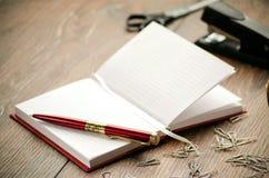 Bloco de notas, pena, grampos, grampeador e tesouras na tabela Imagem de Stock