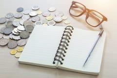 Bloco de notas, pena, vidros e moedas vazios em um fundo claro Fotografia de Stock Royalty Free