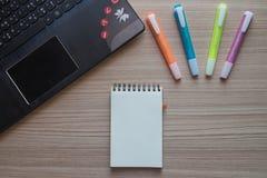 Bloco de notas, penas de marcador e portátil na madeira Imagem de Stock