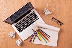 Bloco de notas, portátil e lápis vazios com as folhas do papel amarrotado Fotografia de Stock