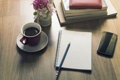 Bloco de notas, smartphone, pena e xícara de café na tabela de madeira Imagens de Stock Royalty Free