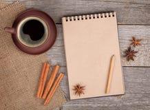 Bloco de notas vazio com copo e especiarias de café na tabela de madeira fotografia de stock royalty free