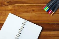 Bloco de notas vazio com a pena colorida na tabela de madeira Fotos de Stock Royalty Free