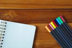 Bloco de notas vazio com a pena colorida na tabela de madeira Imagem de Stock