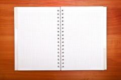 Bloco de notas vazio com a pena na tabela de madeira do escritório Foto de Stock