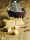 Bloco de queijo parmesão e de ralador fotografia de stock