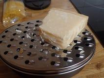 Bloco de queijo parmesão sobre um ralador Imagem de Stock