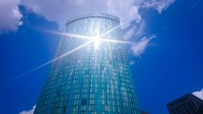 Bloco de torre que reflete o sol sob um céu azul imagem de stock