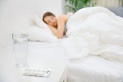 Bloco dos comprimidos na tabela e na mulher que dormem dentro Imagem de Stock