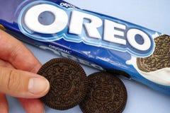 Bloco e cookie de Oreo na mão da mulher imagem de stock