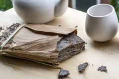 Bloco grande do chá natural preto com uns copo e teakettle imagem de stock