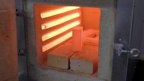 Bloco pequeno do metal colocado na fornalha industrial, parte de metal de incandescência encarnado video estoque