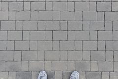 Blocos cinzentos do tijolo com pés do homem Fotografia de Stock