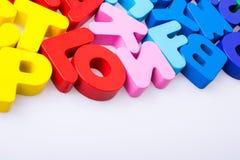 Blocos coloridos da letra dispersados aleatoriamente no branco Foto de Stock