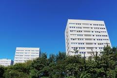 Blocos de apartamentos brancos modernos contra a SK azul imagens de stock