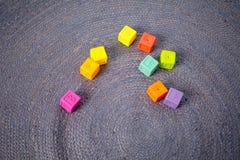Blocos de apartamentos coloridos do ` s das crianças no fundo cinzento imagens de stock