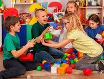 Blocos de apartamentos das crianças no jardim de infância Crianças do grupo que jogam o assoalho do brinquedo fotos de stock royalty free