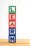 Blocos de apartamentos do alfabeto que soletrando a palavra aprenda Fotos de Stock