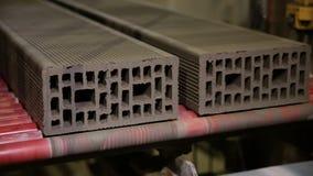 Blocos de apartamentos, produção dos tijolos Transporte com tijolos da construção em uma planta de produção dos tijolos vídeos de arquivo
