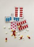 Blocos de comprimidos coloridos nas bolhas e em comprimidos dispersados Imagem de Stock Royalty Free